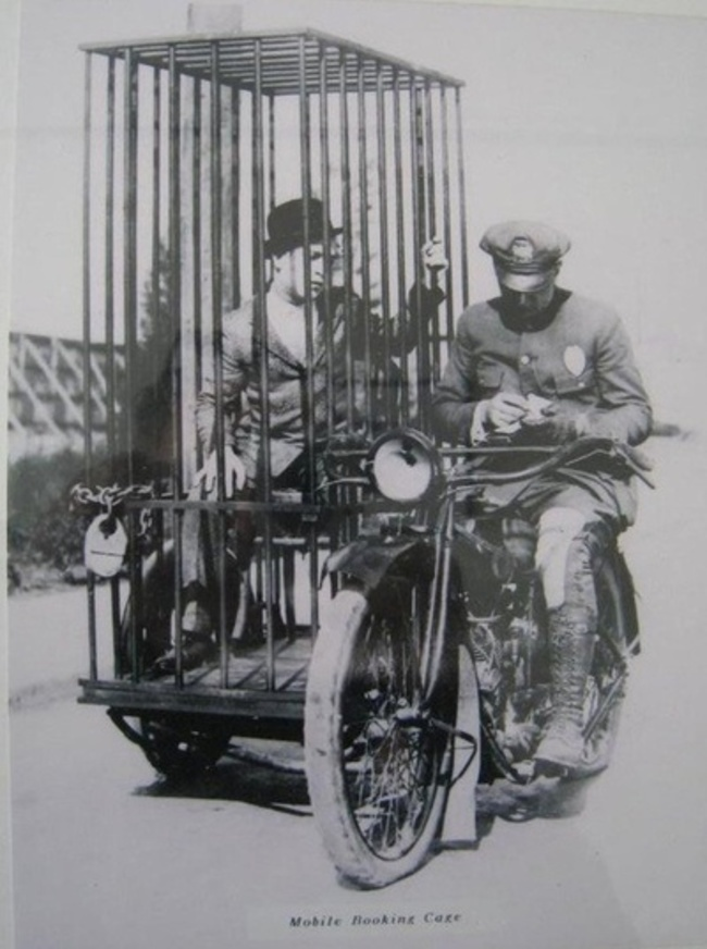 19.-A-police-officer-on-a-Harley-and-an-old-fashioned-mobile-holding-cell.-1921